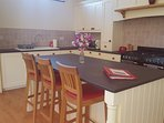 Solid wood kitchen with granite worktops and central island.