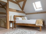 upstairs bedroom with king bed, lounge area and balcony with views across the valley