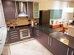 Beautiful well equipped kitchen with black granite counter-top and laundry closet