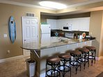 Fully furnished kitchen with bar seating.