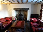 Sitting room with log burner in inglenook hearth with slate floor.