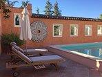 Teak sunbeds and umbrella beside pool.