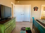 Large spacious master bedroom with TV, sliding doors to deck, king-sized bed, luxurious linens.