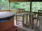 Covered deck with large round hot tub and BBQ grill