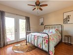Bedroom with queen bed with french doors out to patio overlooking a beautiful pasture