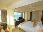 Master bedroom with king bed and private bathroom, ocean in background.