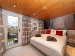Mistletoe Boutique Lodge's Master King size bed with side door leading to hot tub and sunny terrace