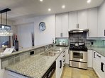 Modern kitchen featuring granite counter tops, stainless steel appliances and a breakfast bar