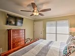 The master bedroom features large windows, a flat-screen TV, and king bed.