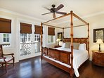 Elegant master suite features canopy King Tommy Bahama bed