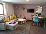 Spacious open plan lounge with corner sofa, smart tv, alexa and dining area