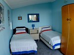 Bedroom 2 with 2 single beds and a single chair bed.