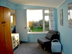 Bedroom 2 with 2 single beds and single chair bed ( shown). View to garden, beach & sea.