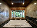 Master en-suite sunken bath enjoys garden and sea views.