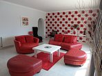 a rotating red leather two seater cuddle chair to cosy up inl