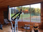 wellness gym with tennis court and summer house in background