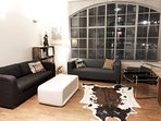 Spacious living room with loft-style giant windows, sofabed and sofa