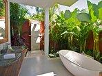 Downstairs bathroom with bathtub and open air rain shower.