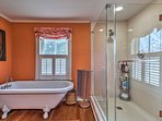 This vibrant bathroom offers a walk-in shower and a bathtub.