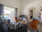 De woonkamer,  met een 2 zitbank, relax stoelen, salontafel, tv meubel, dressoir en vitrinekast