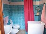 bagno con doccia e lavatrice. l'appartamento include un ulteriore bagno con doccia e wc