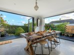 Contemporary dining space opens to garden/terrace