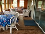 Glassed in porch extends sitting and eating space.