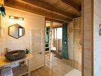 douche à l'italienne, vasque du lavabo en pierre et sèche-serviette