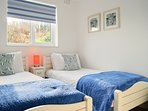 A light and airy 2nd bedroom with twin beds, cosy throws and drawer and hanging space