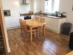 Homely open plan, perfectly equipped kitchen area with sturdy extending dining table which sits 4