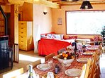 Grand séjour autour d'un poêle à granulé, ouvert sur une cuisine et un salon