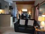 Open plan lounge with high vaulted ceilings and patio doors leading on to balcony.