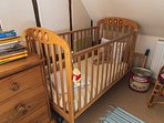 Wooden cot in twin room. An additional travel cot can be provided if required.