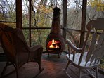 Screened back porch with a chiminea fireplace.