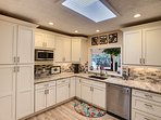 Bright kitchen serving and clean-up area, with skylight and counter pass through to dining room.