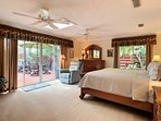 Poolside master suite with king bed, skylight, twin ceiling fans and large bath.