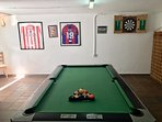 Pool table and darts board.