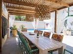 Eettafel met 10 stoelen kijkt onder de koele veranda direct uit op het zwembad