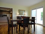 Dining area is an open space, close to kitchen with glass sliding doors out to deck and grill.