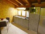 Cocina con lavavajilla, lavadora, vitro, microondas, frigo y pequeños electrodomèsticos.