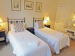 Spacious room with comfortable, ornate brass beds, and prints of Old Edinburgh.