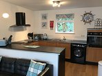 Kitchen with washer/dryer, dishwasher, fridge and freezer. Microwave, oven and hob