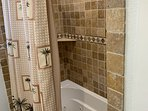 Full size tub and shower with stone tile surround.