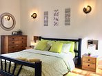 Spacious bright bedroom has a cooling breeze flow thru from the French doors to the window opposite.