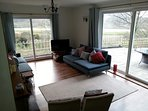 Sitting room with open fire, modern sofas and spectacular view of the estuary and mountains