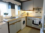 Compact and well equipped kitchen with electric cooker, washing machine and fridge.
