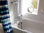 Bathroom with shower over bath. Quality towels provided
