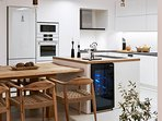 A wine cooler and built-in appliances are at your disposal.