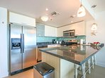 Full-sized fully equipped kitchen with 4-bar stools