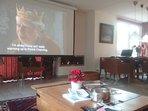 woonkamer met projector en groot scherm in gebruik
